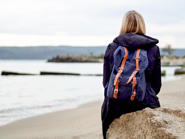 Mulher com mochila na beira-mar
