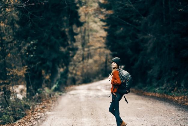 Mulher com mochila na estrada na floresta em modelo de árvores altas com paisagem de outono