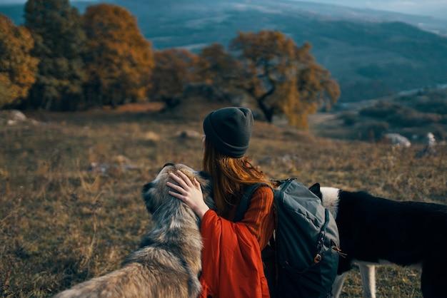 Mulher com mochila na natureza ao lado de passear com o cachorro amizade