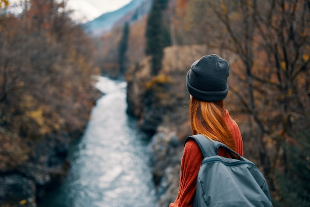 Mulher com mochila na natureza na ponte perto da aventura de montanhas do rio. foto de alta qualidade