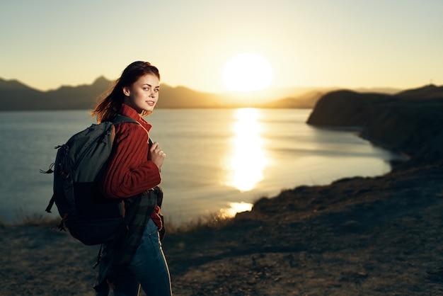 Mulher com mochila na natureza, nossa viagem ao pôr do sol
