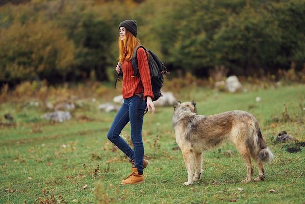 Mulher com mochila nas costas cão de passeio de turismo natural