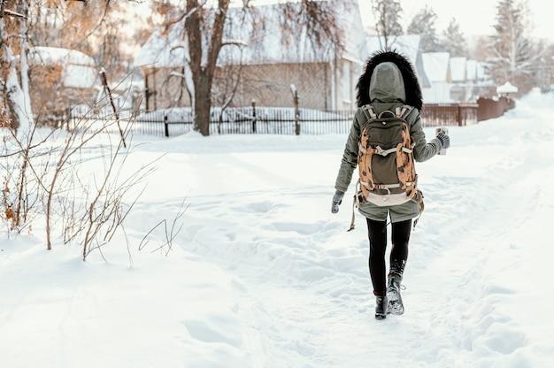 Mulher com mochila nas costas no dia de inverno