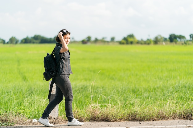 Mulher com mochila pedindo carona ao longo de uma estrada