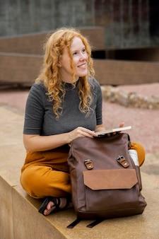 Mulher com mochila segurando um diário
