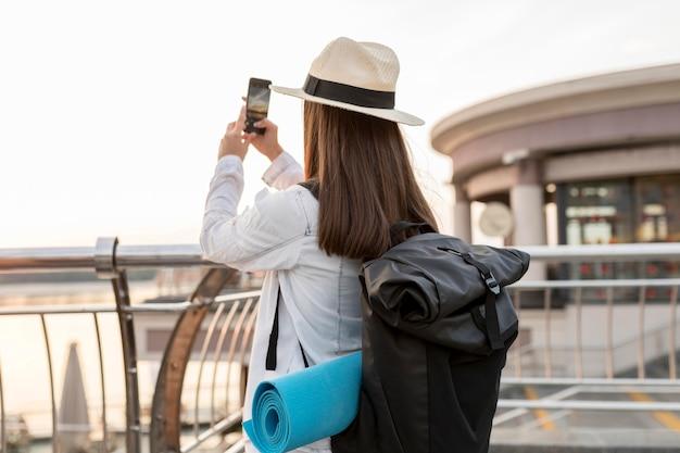 Mulher com mochila tirando fotos enquanto viaja