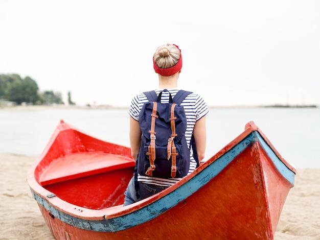Mulher com mochila viajando com barco