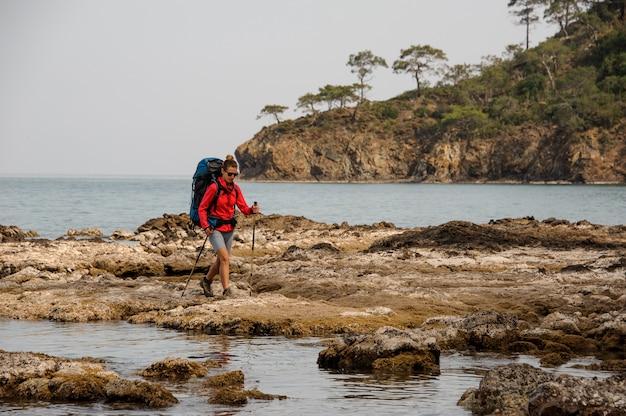 Mulher com mochila viajando na costa do mar