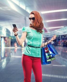 Mulher com muitas bolsas de atirar usando o telefone no shopping center