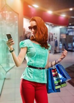 Mulher com muitas bolsas de atirar usando o telefone no shopping