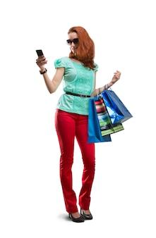 Mulher com muitas bolsas de atirar usando telefone isolado no branco