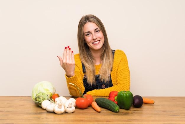 Mulher com muitos legumes convidando para vir