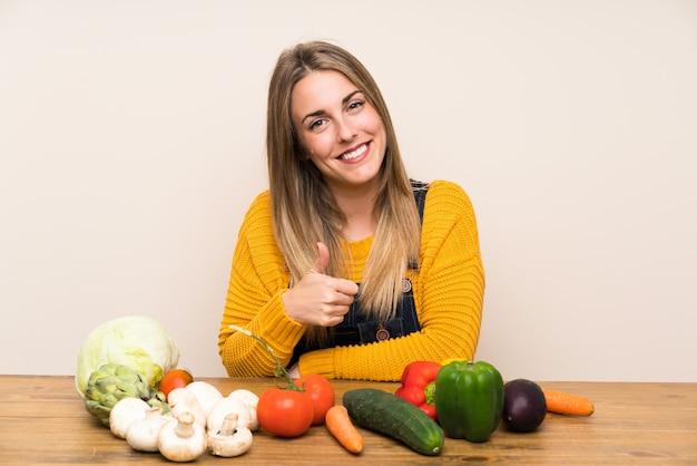 Mulher com muitos legumes dando um polegar para cima gesto