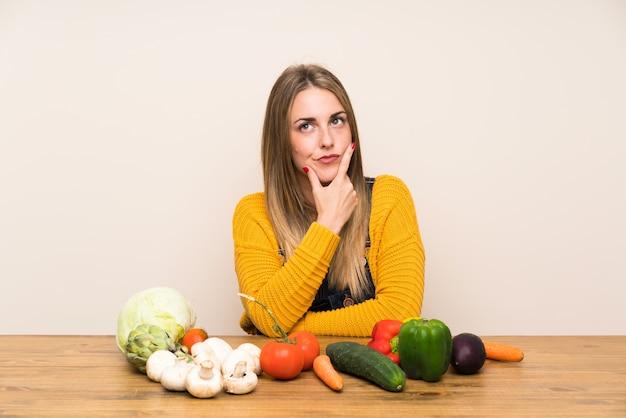 Mulher com muitos legumes em pé e pensando uma idéia