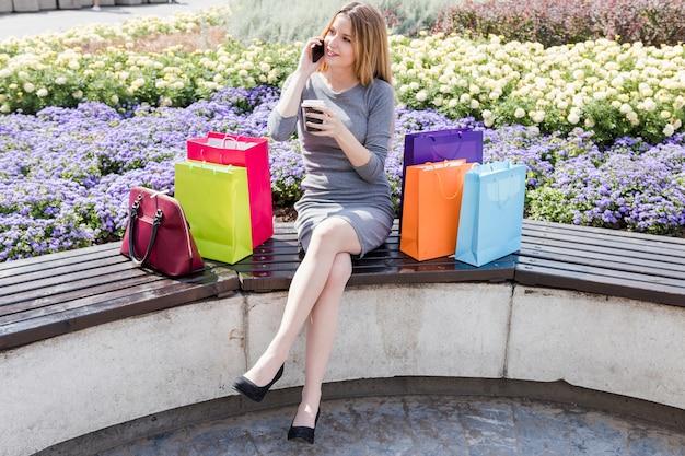 Mulher com multi coloridas sacolas de compras, falando no celular no parque