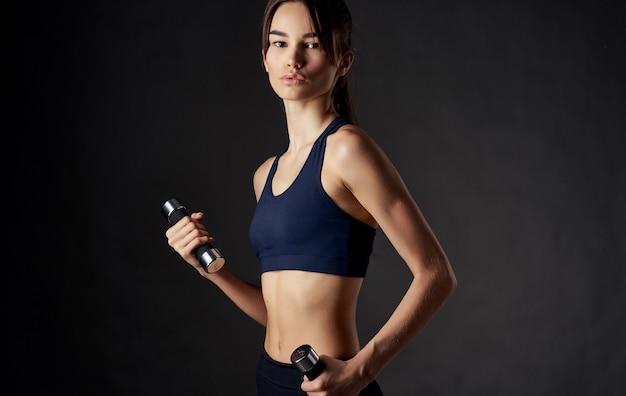 Mulher com músculos fazendo halteres esportivos nas mãos e corpo esguio.