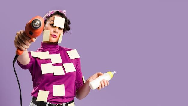 Mulher com notas auto-adesivas nela segurando a broca e mamadeira