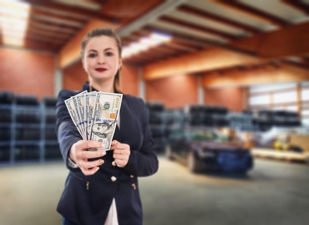 Mulher com notas de dólar e carro novo na estação de serviço