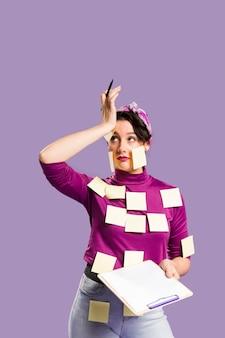 Mulher com notas sobre ela segurando uma prancheta