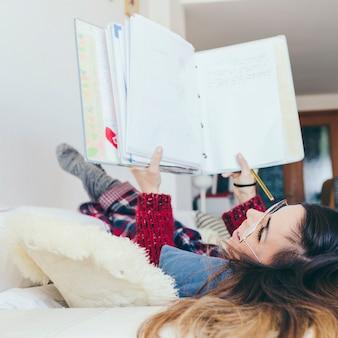 Mulher com o bloco de notas deitado no sofá