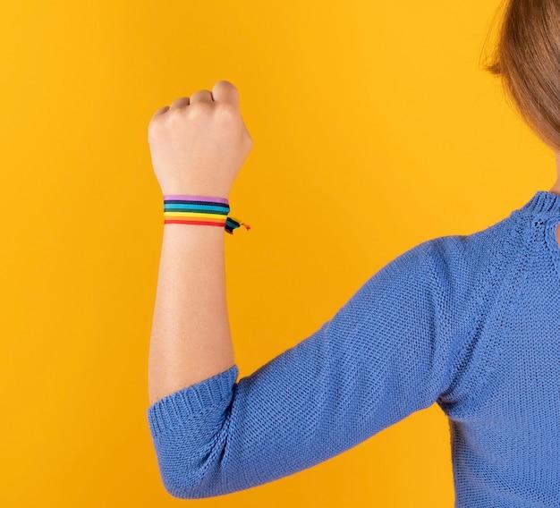Mulher com o braço levantado e bandeira do orgulho gay