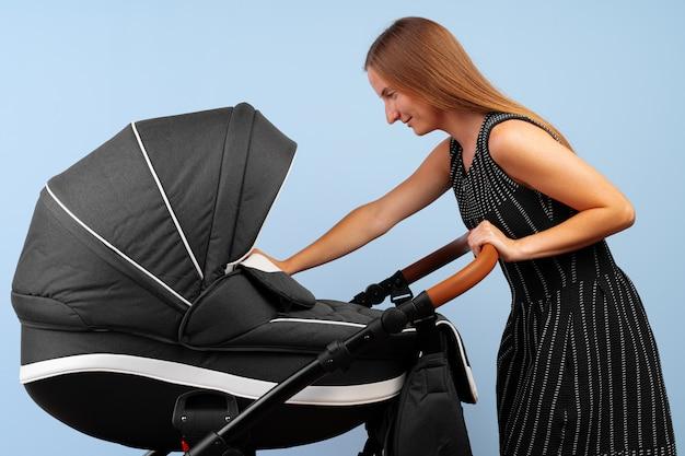 Mulher com o carrinho de bebê no quarto. fechar-se.