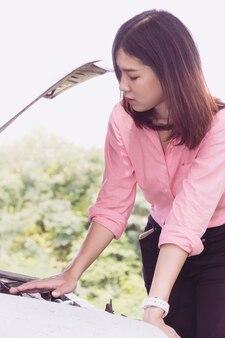 Mulher com o carro quebrado na estrada à espera de ajuda.
