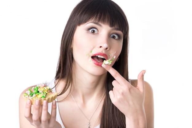 Mulher com o dedo completa um bolo