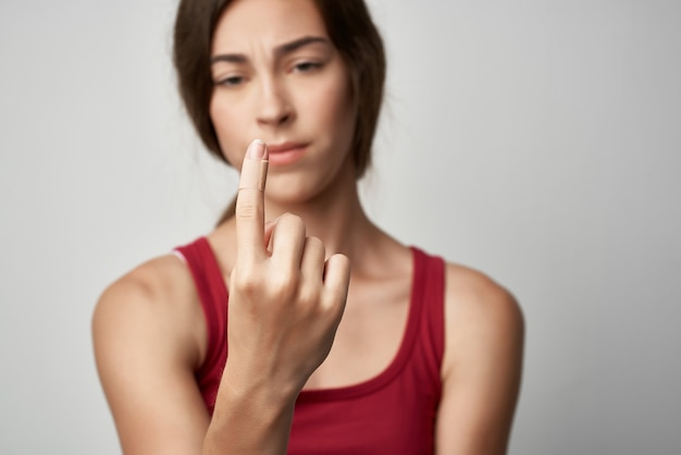 Mulher com o dedo indicador ferido, ferimento, medicamento, fundo claro