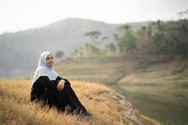 Mulher com o hijab sentado ao ar livre