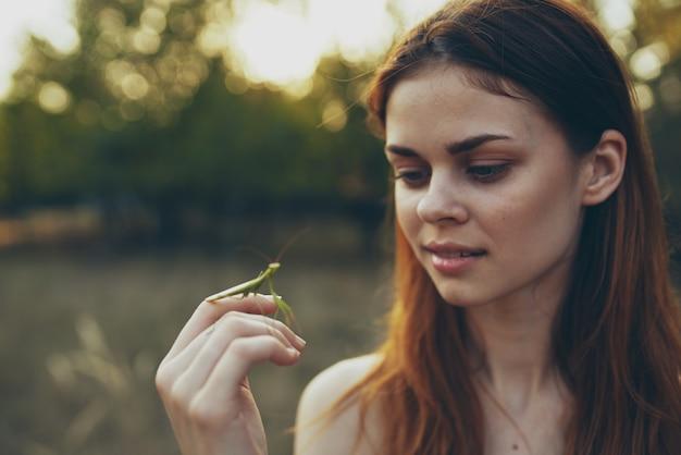 Mulher com o inseto na mão orando o verão de árvores da natureza do mantis.