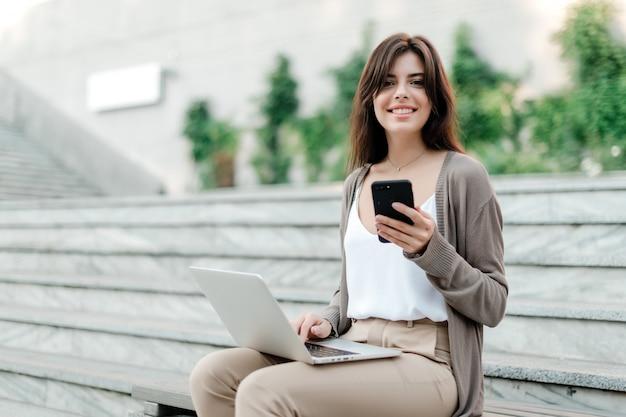 Mulher com o laptop ao ar livre nas escadas