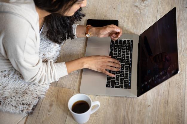 Mulher com o laptop on-line em casa tomando café, com telefone celular