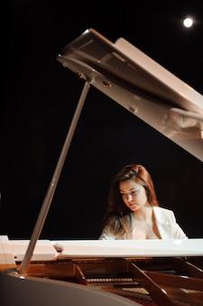Mulher com o piano branco no palco.