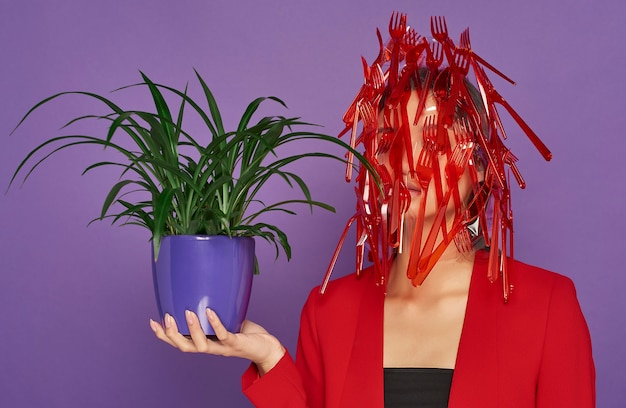 Mulher com o rosto coberto de plástico enquanto segura uma planta