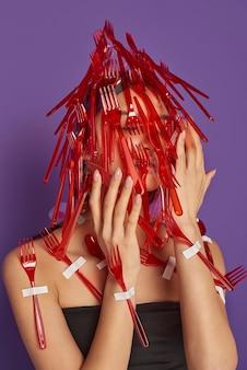 Mulher com o rosto coberto por garfos e colheres de plástico