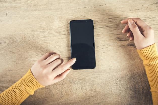 Mulher com o telefone inteligente na mesa de madeira