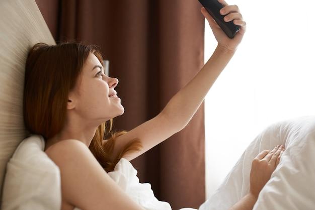 Mulher com o telefone na mão na cama perto da cortina da janela