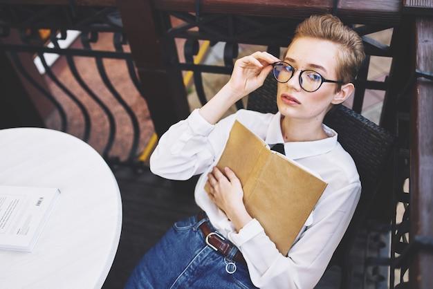 Mulher com óculos ao ar livre em um café de verão.