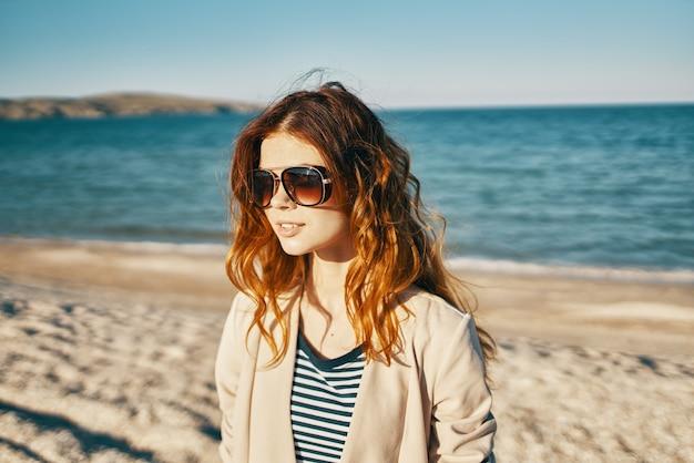 Mulher com óculos cabelo ruivo modelo bege jaqueta areia praia mar
