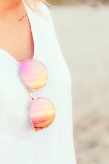 Mulher com óculos cor de rosa na praia