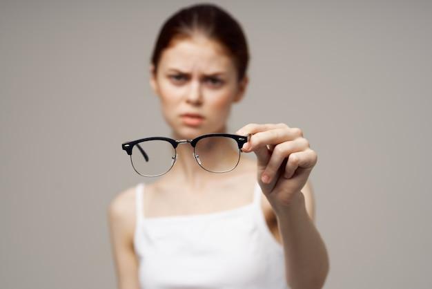Mulher com óculos de camiseta branca nas mãos do astigmatismo de fundo claro