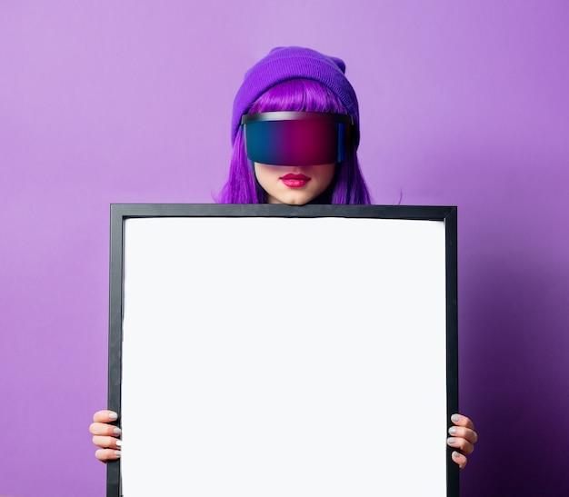 Mulher com óculos de realidade virtual, agasalho esportivo dos anos 80 e moldura de maquete na parede violeta