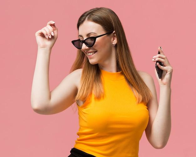 Mulher com óculos de sol dançando