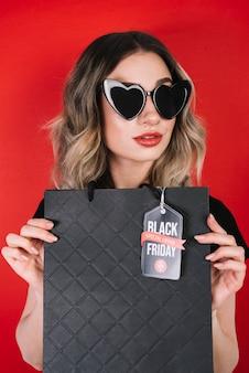 Mulher com óculos de sol de coração e bolsa de sexta-feira preta