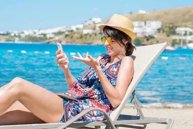 Mulher com óculos de sol e chapéu que olha um móbil