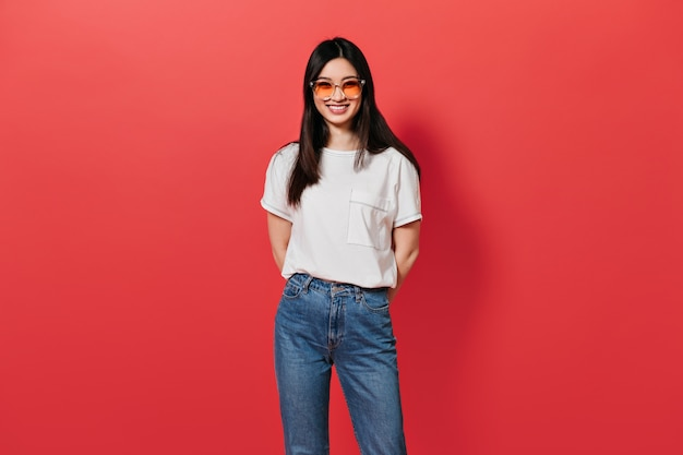 Mulher com óculos de sol laranja sorrindo na parede vermelha