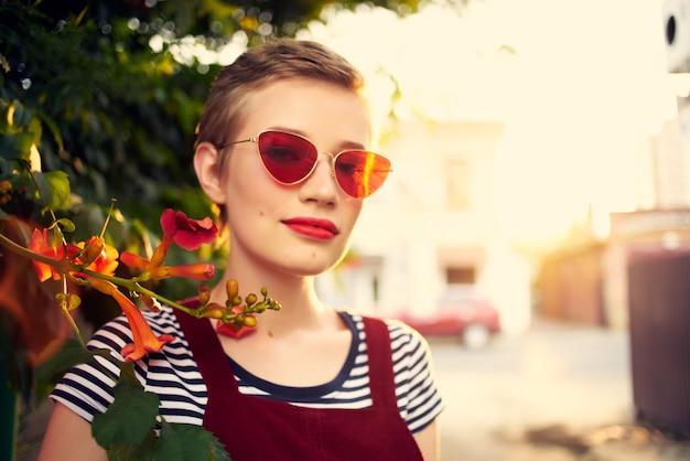 Mulher com óculos de sol na rua perto de flores posando estilo de vida