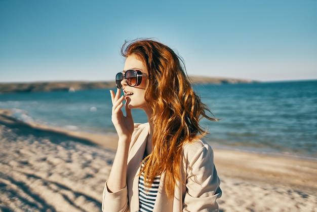 Mulher com óculos de sol no verão olha para o lado perto do mar nas montanhas verão