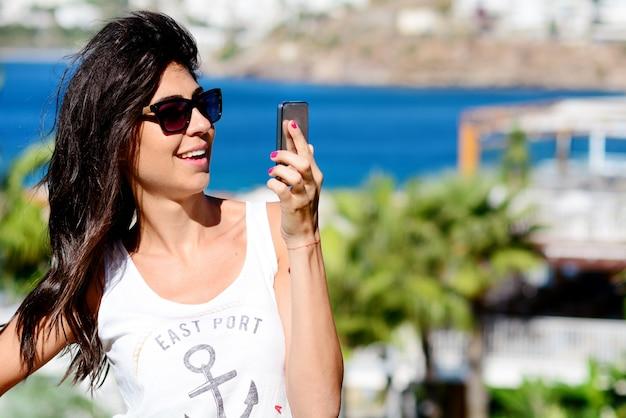 Mulher com óculos de sol olhando para o celular